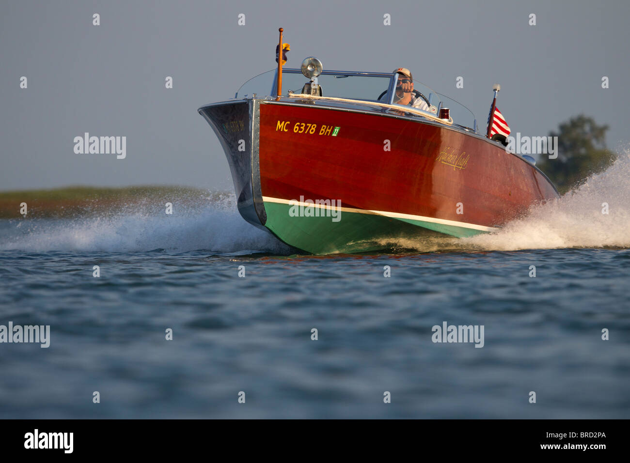 An approaching antique, wooden Hackercraft speedboat. - Stock Image
