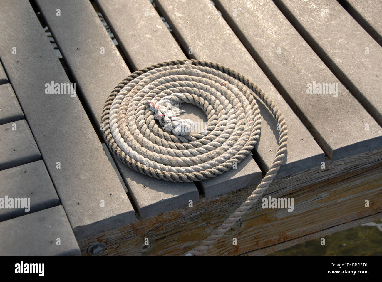 A coiled rope on the marina boatdock. Photo taken with a Nikon D200 camera. - Stock Image