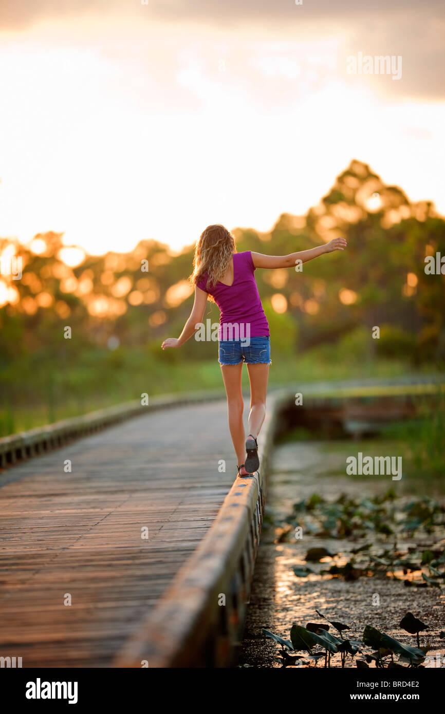 Young girl balancing on a bridge - Stock Image
