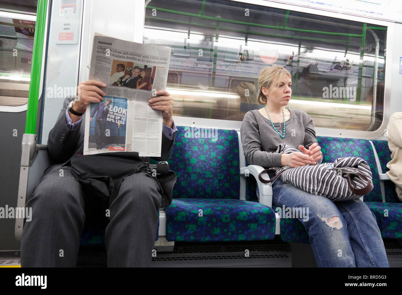 male passenger reading newspaper with bored looking woman seated on London Underground - Stock Image