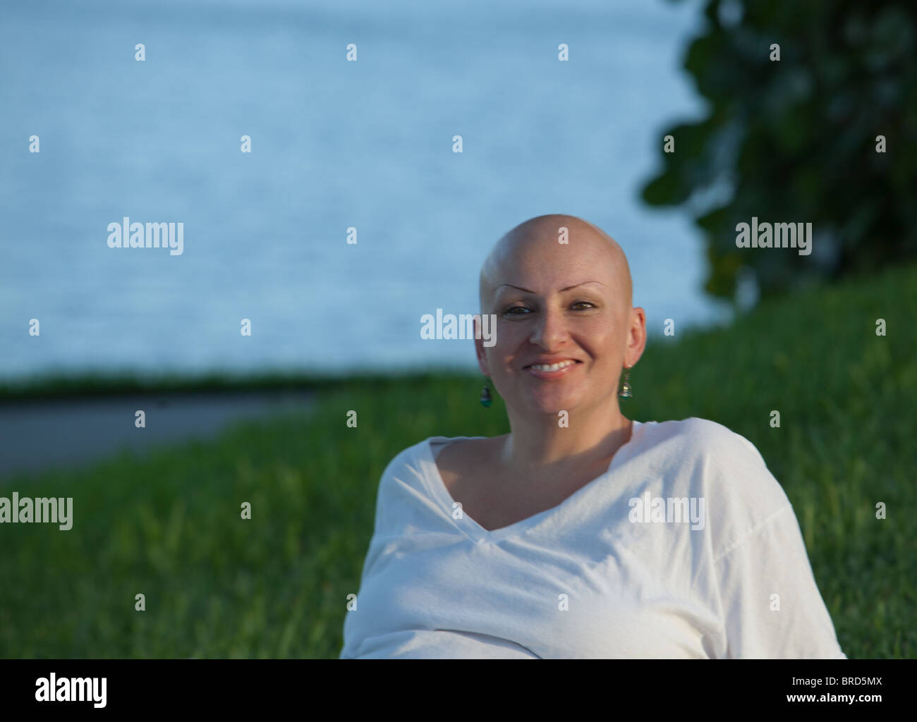 A cancer survivor smiles during an afternoon at the park - Stock Image