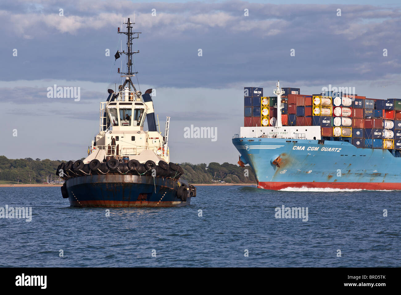 Tug boats with container ship ready to dock at Southampton - Stock Image