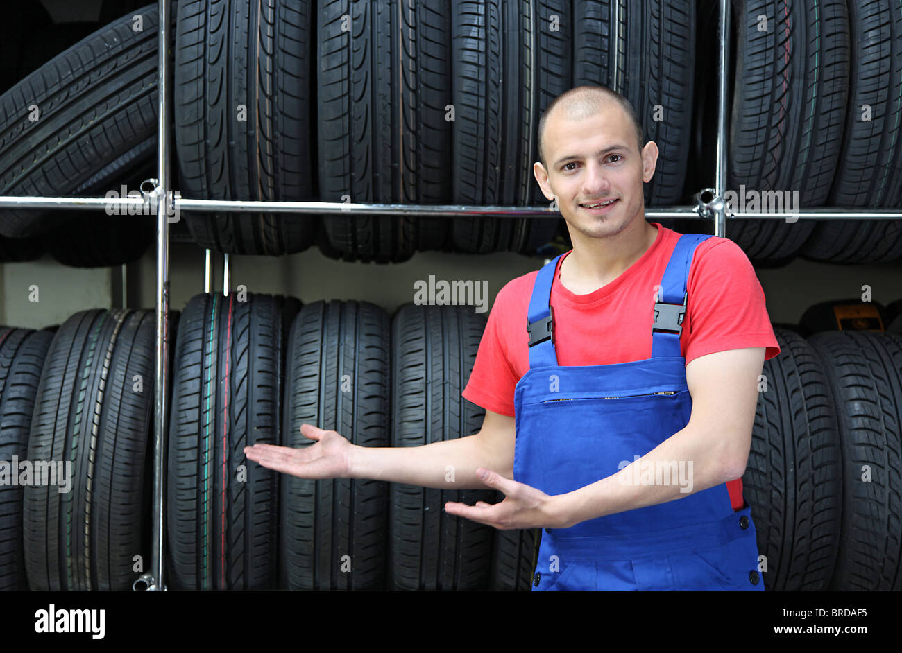 A smiling mechanic in a garage standing next to a rack full of tires and making a positive gesture - Stock Image