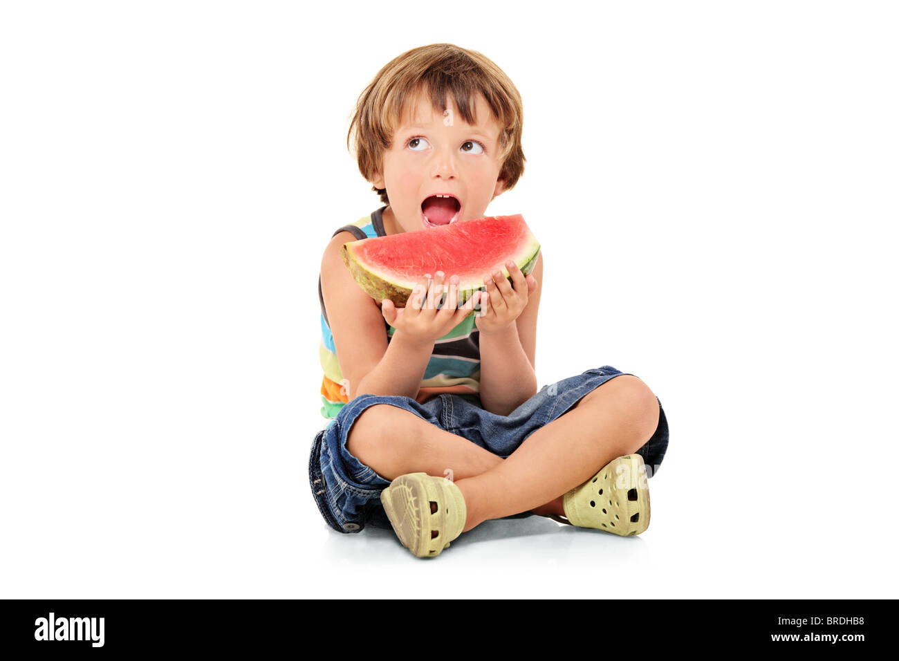 A young boy holding a slice of watermelon - Stock Image