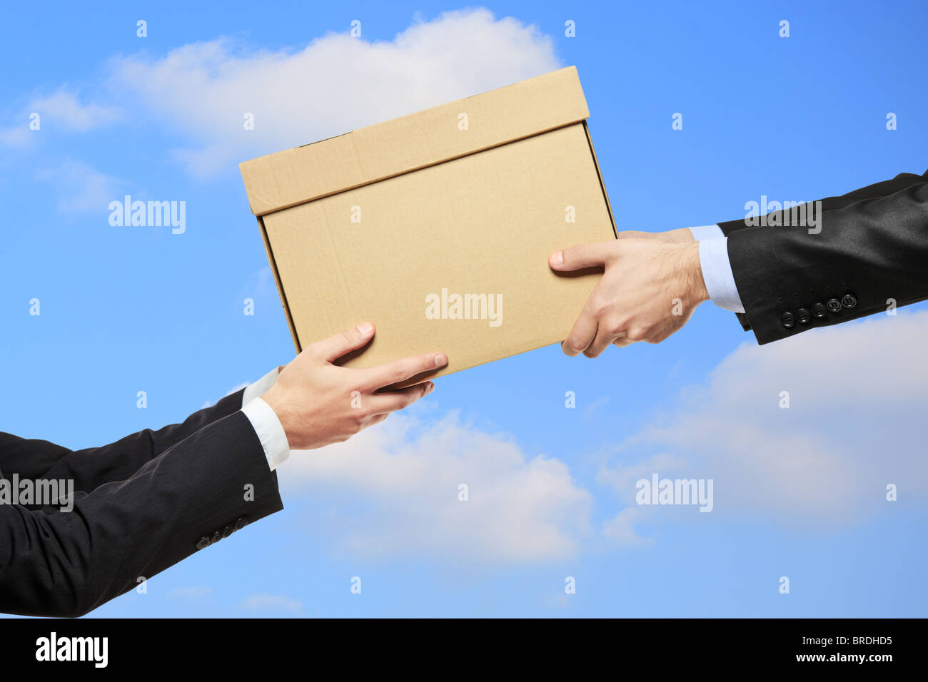 A businessman delivering a package to a man - Stock Image