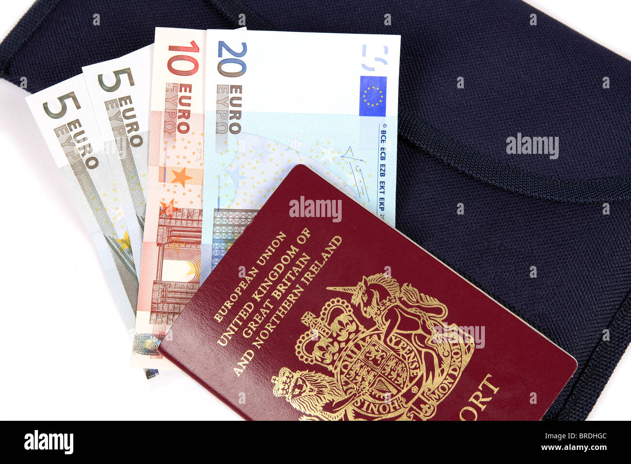 Euro money a British Passport and a travel Wallet set against a white background - Stock Image
