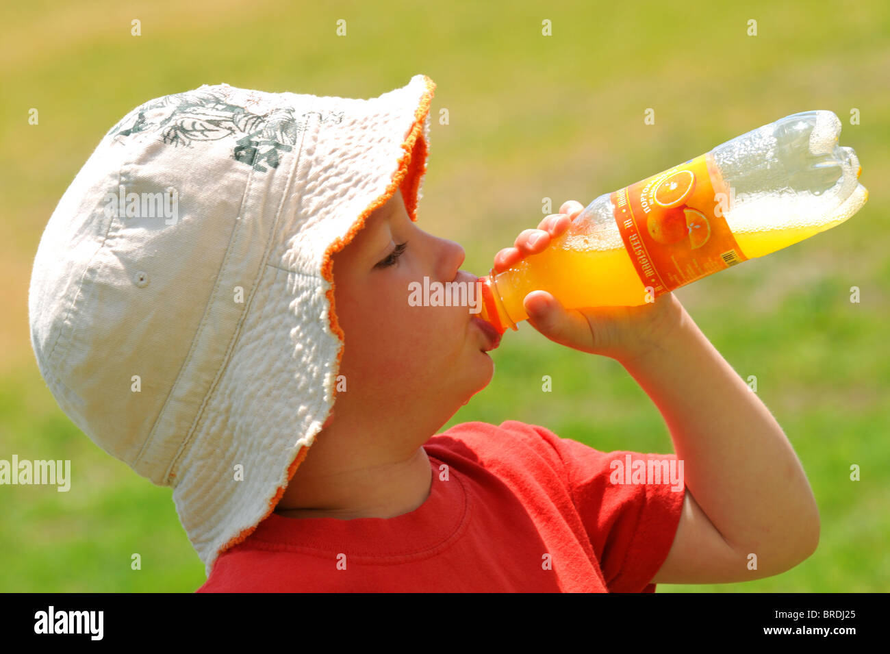 Boy drinking out of a plastic bottle, thirst, thirsty child drinking Stock Photo