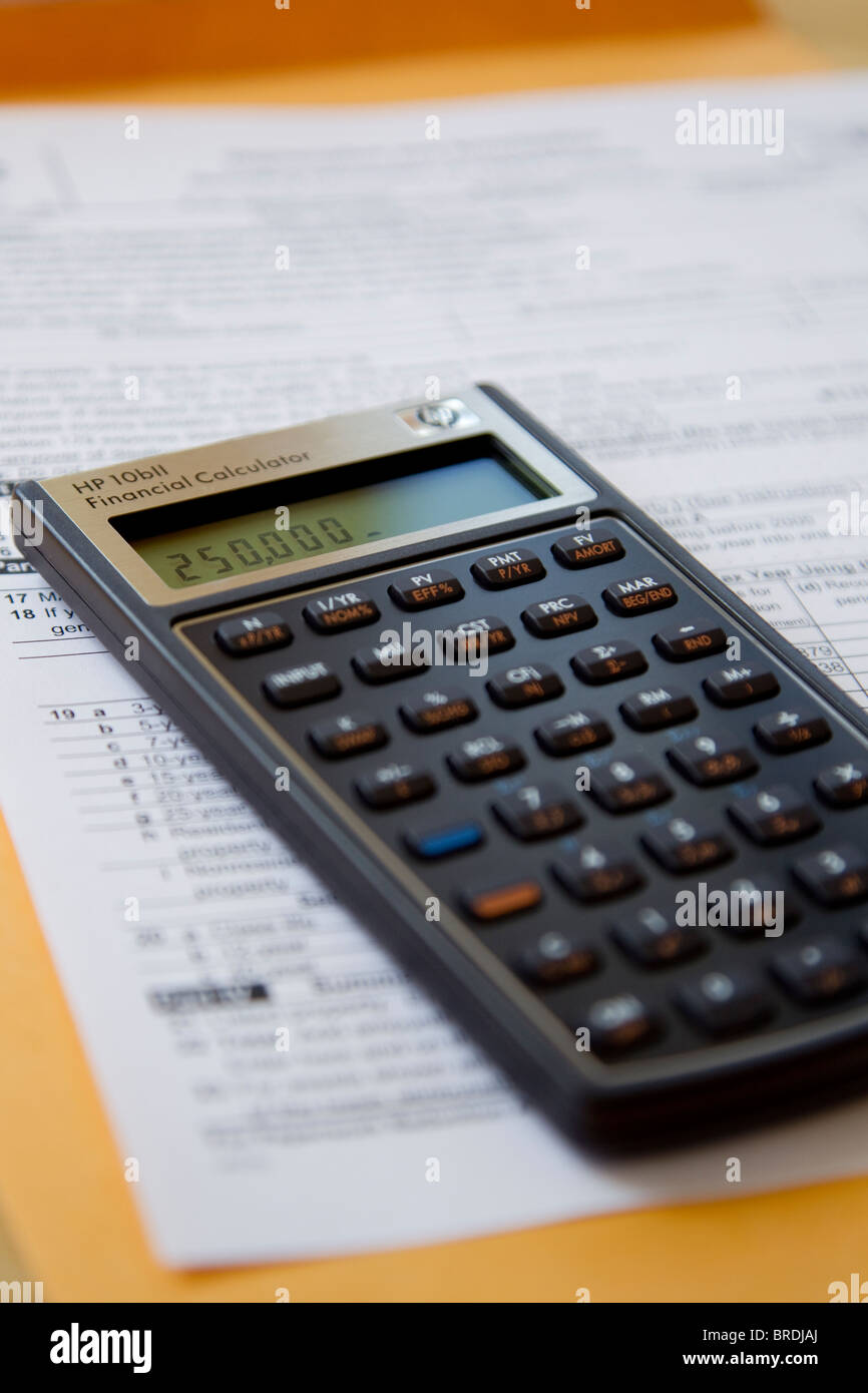 Calculator calculating income taxes on tax form, expenses and income - Stock Image