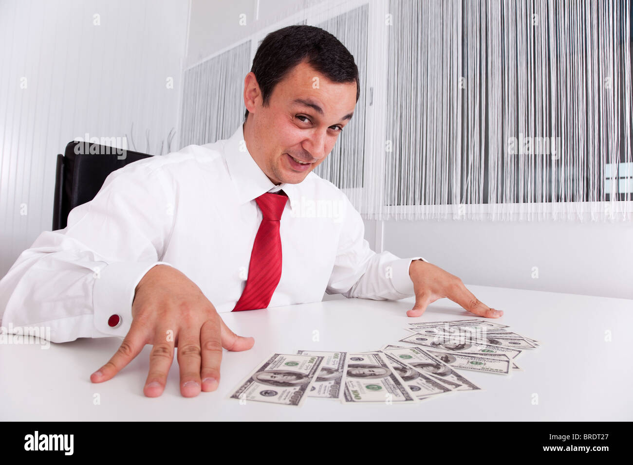 Businessman at the office enjoying his money - Stock Image