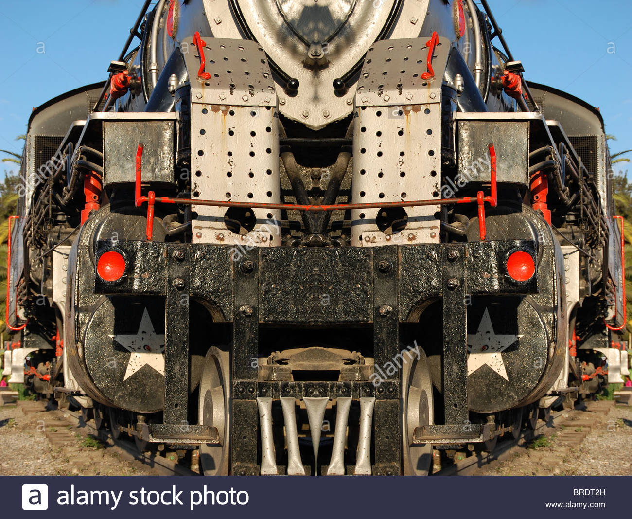 composite image train trains locomotive looking directly at front cattle guard grate showing massive steel construction Stock Photo