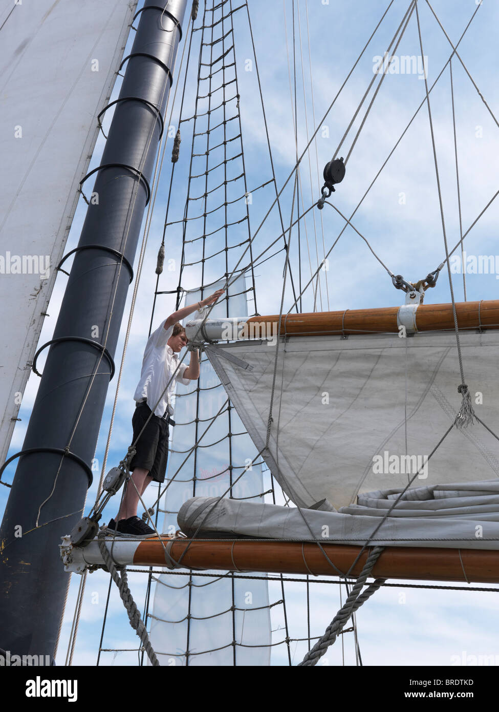 Sailor on a tall ship folding a sail - Stock Image