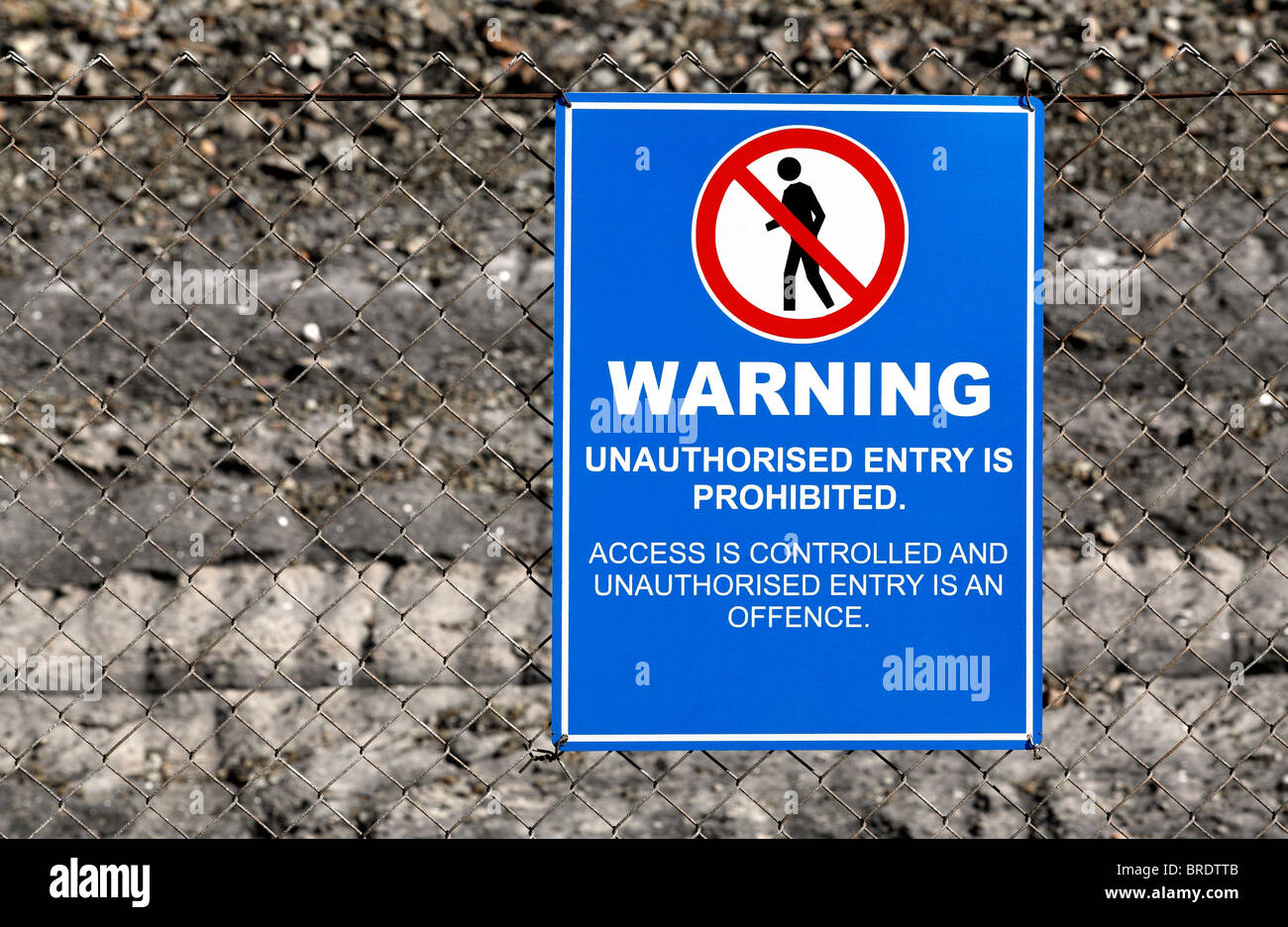 A warning sign on a wire fence with blue background and a black figure of a person with a red slashed circle - Stock Image