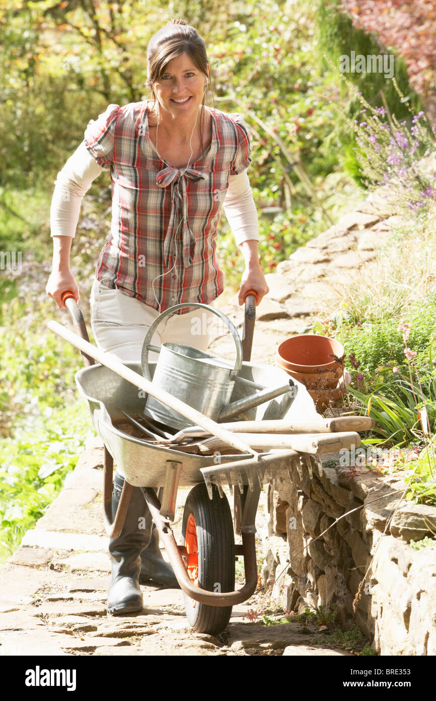 Woman With Wheelbarrow Working Outdoors In Garden - Stock Image