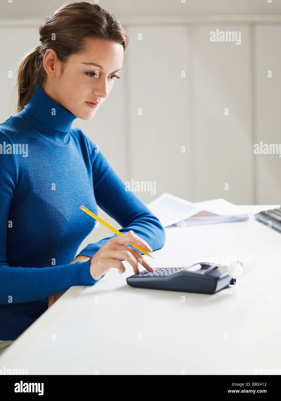 woman using calculator in office Stock Photo