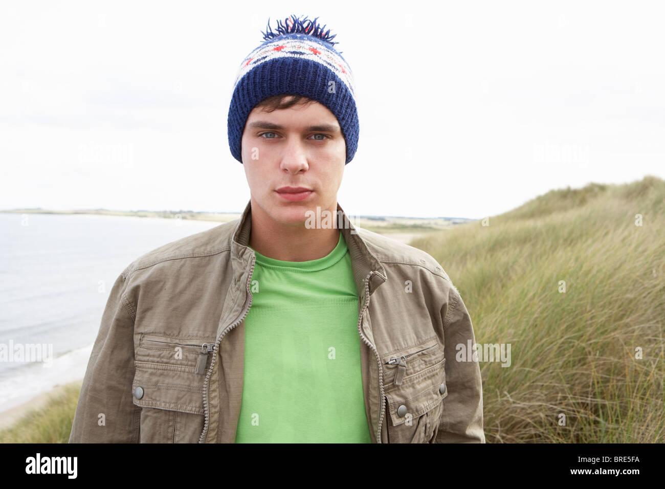 Teenage Boy Standing In Sand Dunes Wearing Woolly Hat - Stock Image