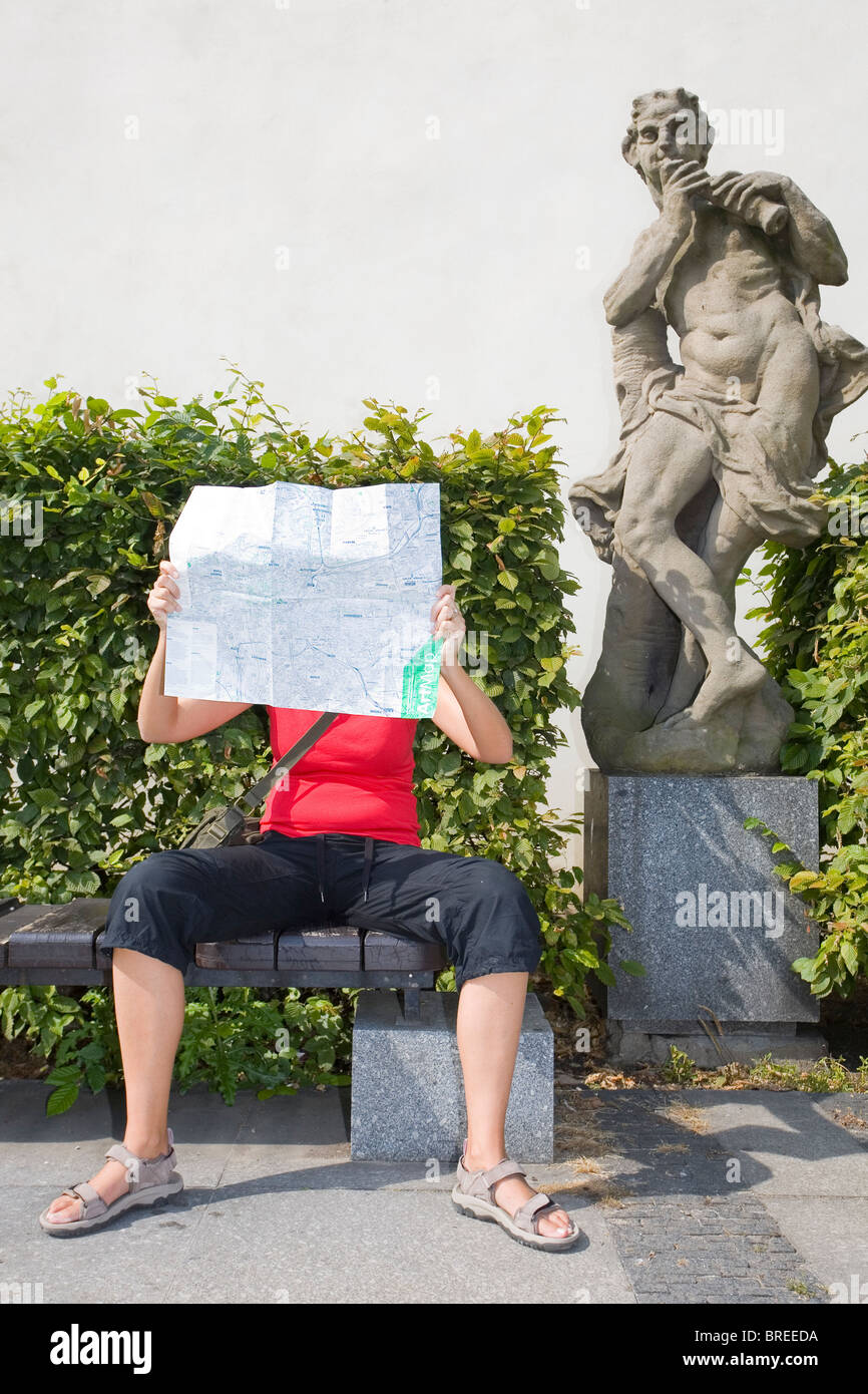 Woman lost in Prague with a map and a confused looking statue - Stock Image