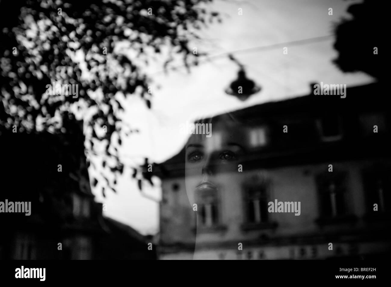 Romania, Transylvania Sibiu. Femal face reflection on a window glass - Stock Image