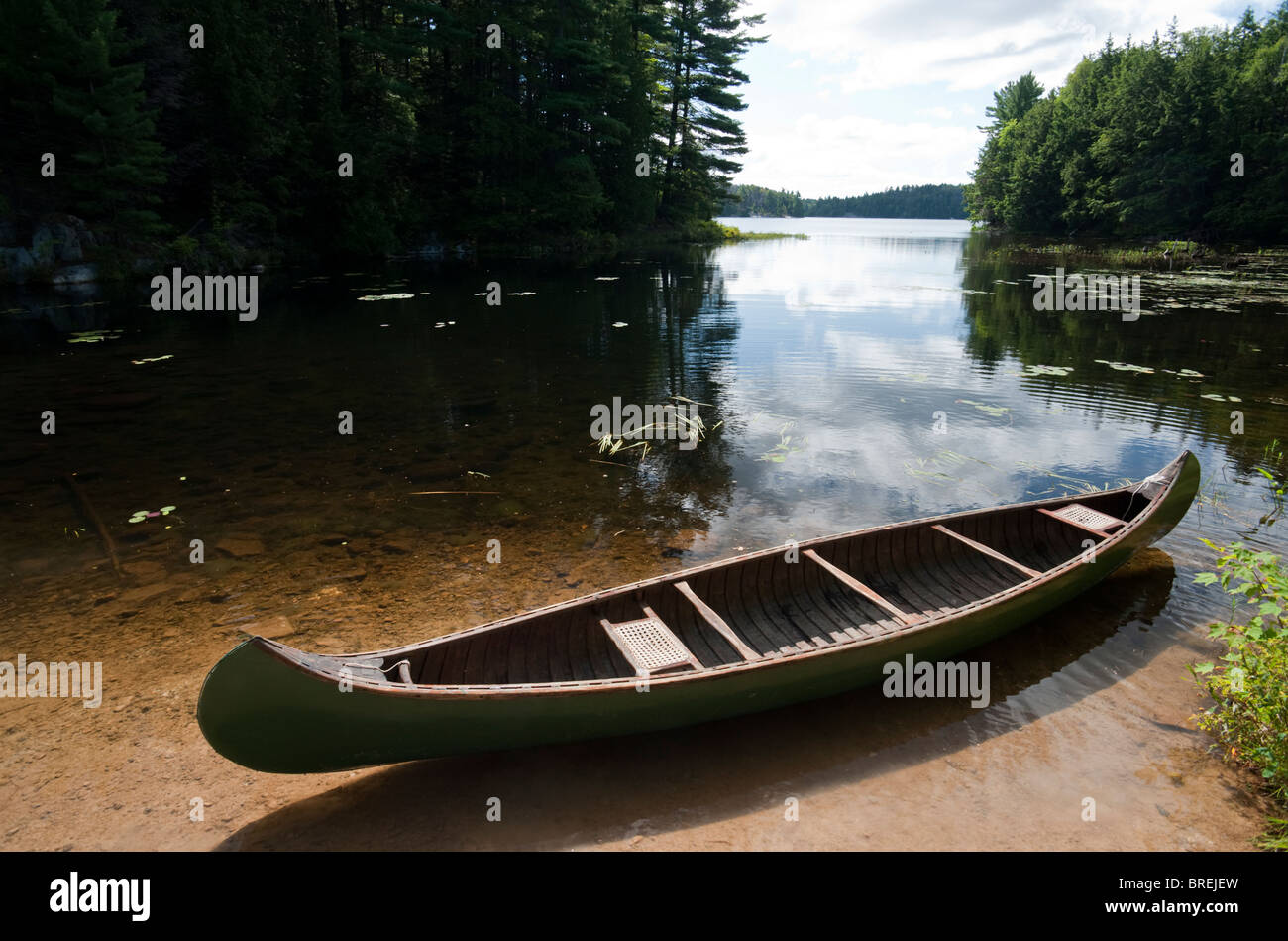 A traditional wooden cedar strip canoe at the edge of a portage in Killarney Provincial Park. - Stock Image