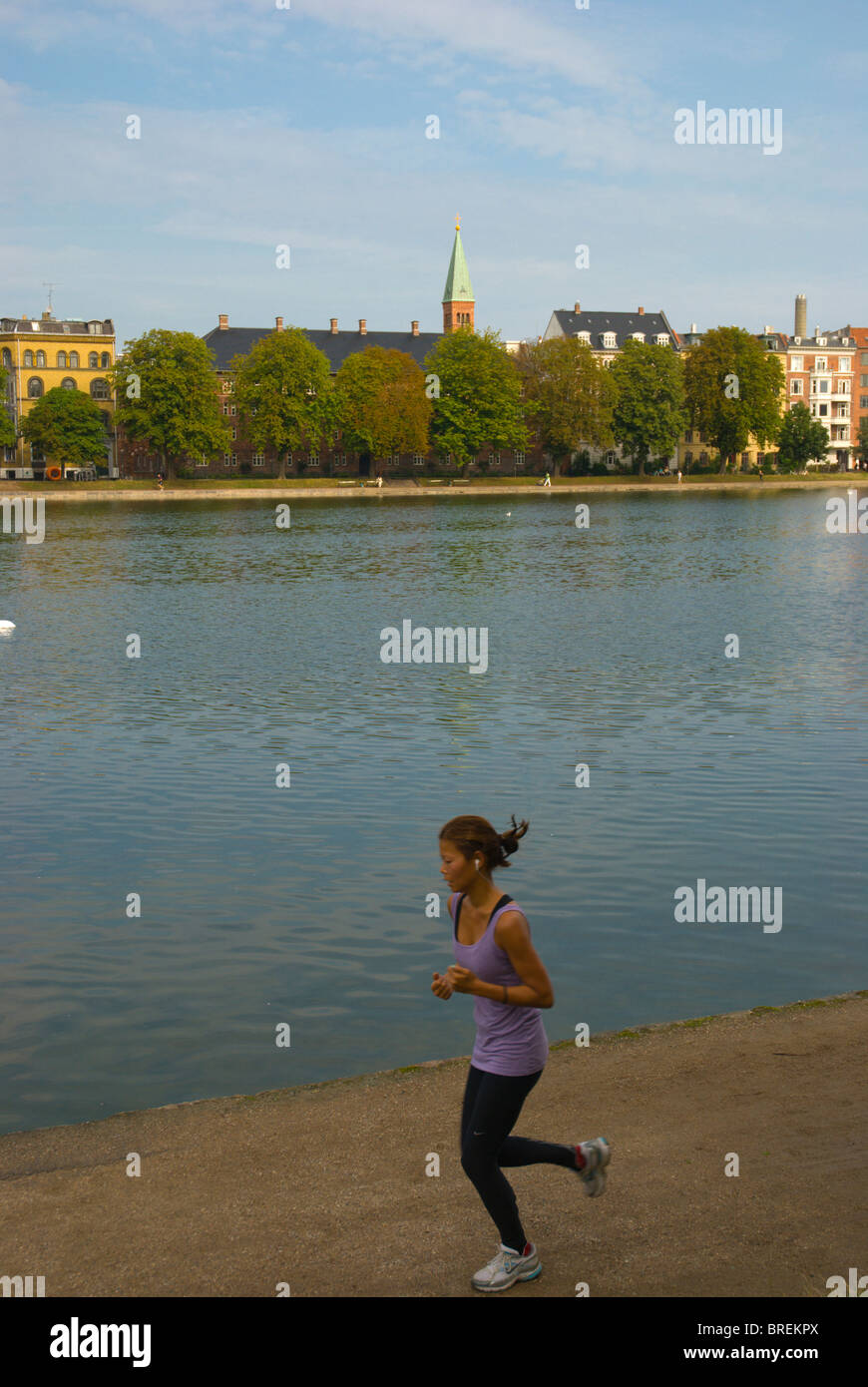 Female jogger along Sortedams So man-made lake central Copenhagen Denmark Europe - Stock Image