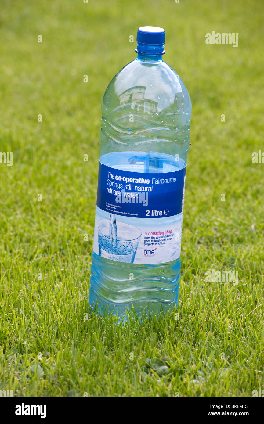 Half empty plastic mineral water bottle on a green lawn. - Stock Image