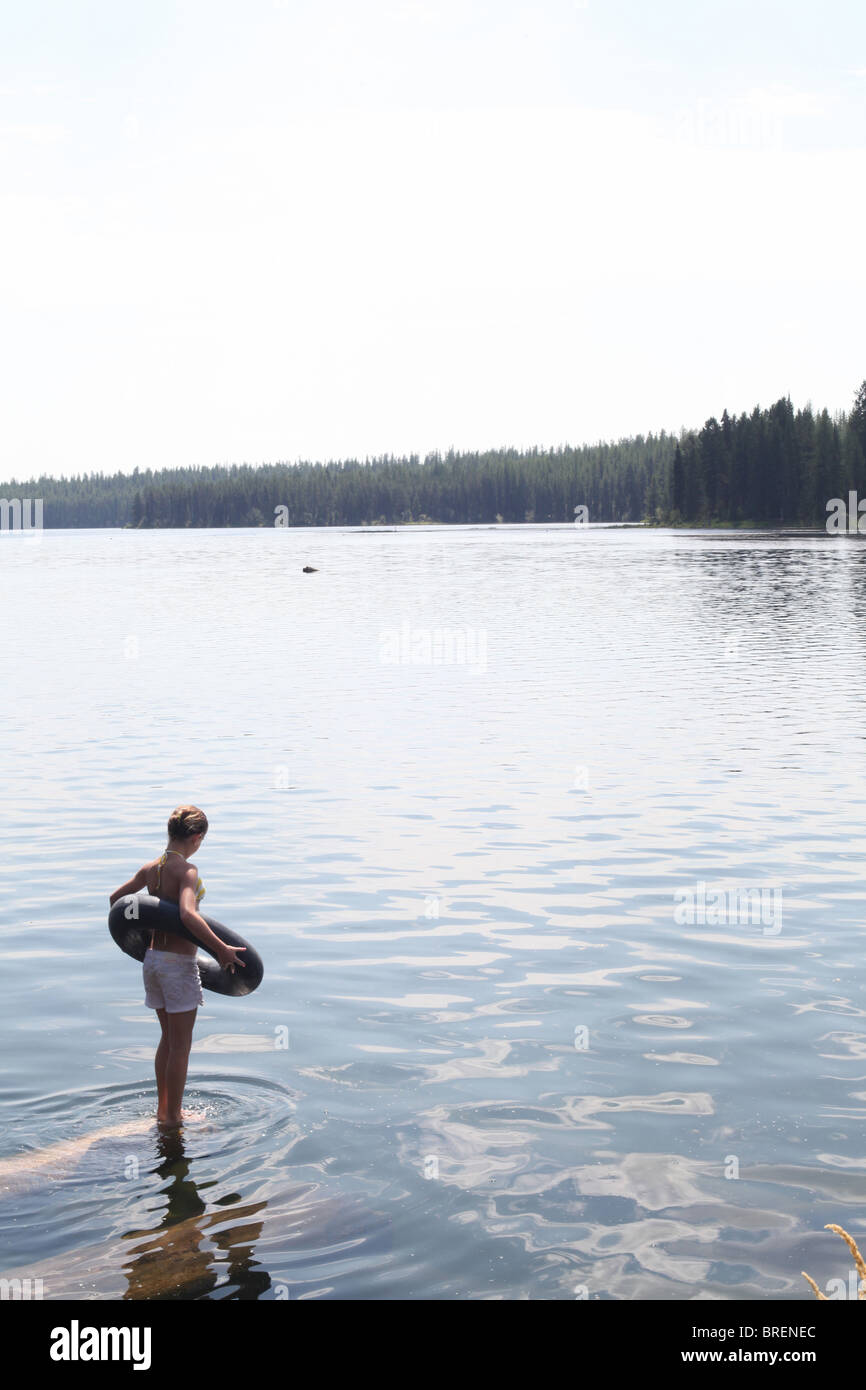teen girl standing on log w/ inner tube ready to jump into lake - Stock Image