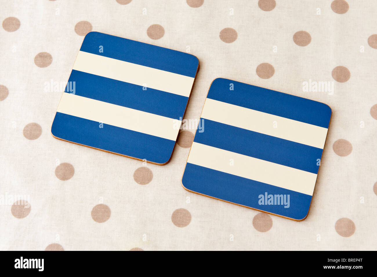 Two blue and cream striped coaster place mats on a cream and brown spotted plastic tablecloth - Stock Image