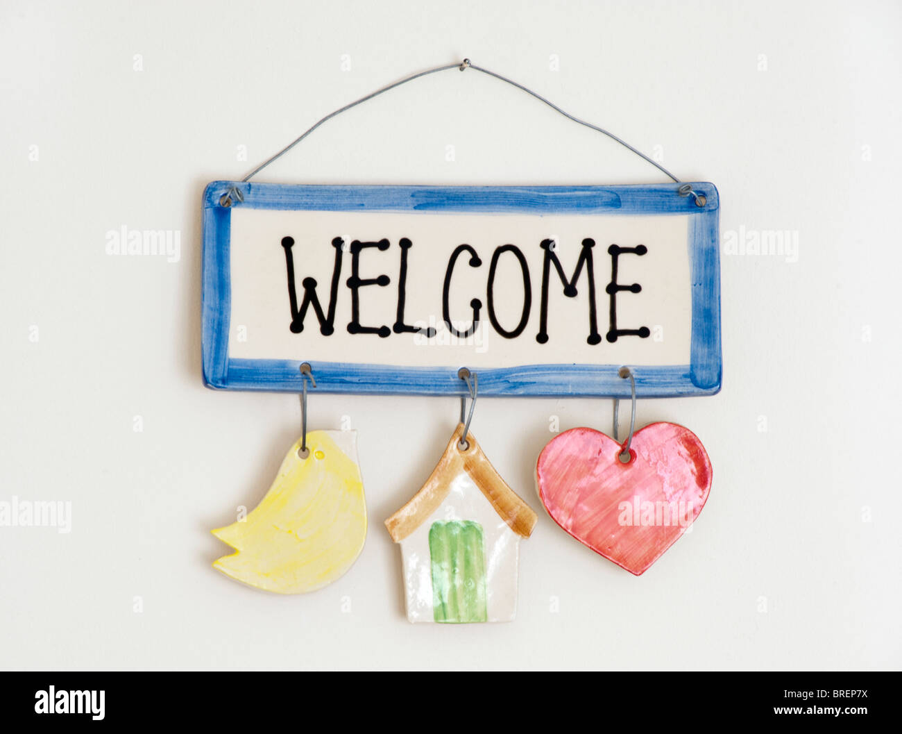 Ceramic welcome plate hanging on a nail and wire on a cream wall - Stock Image