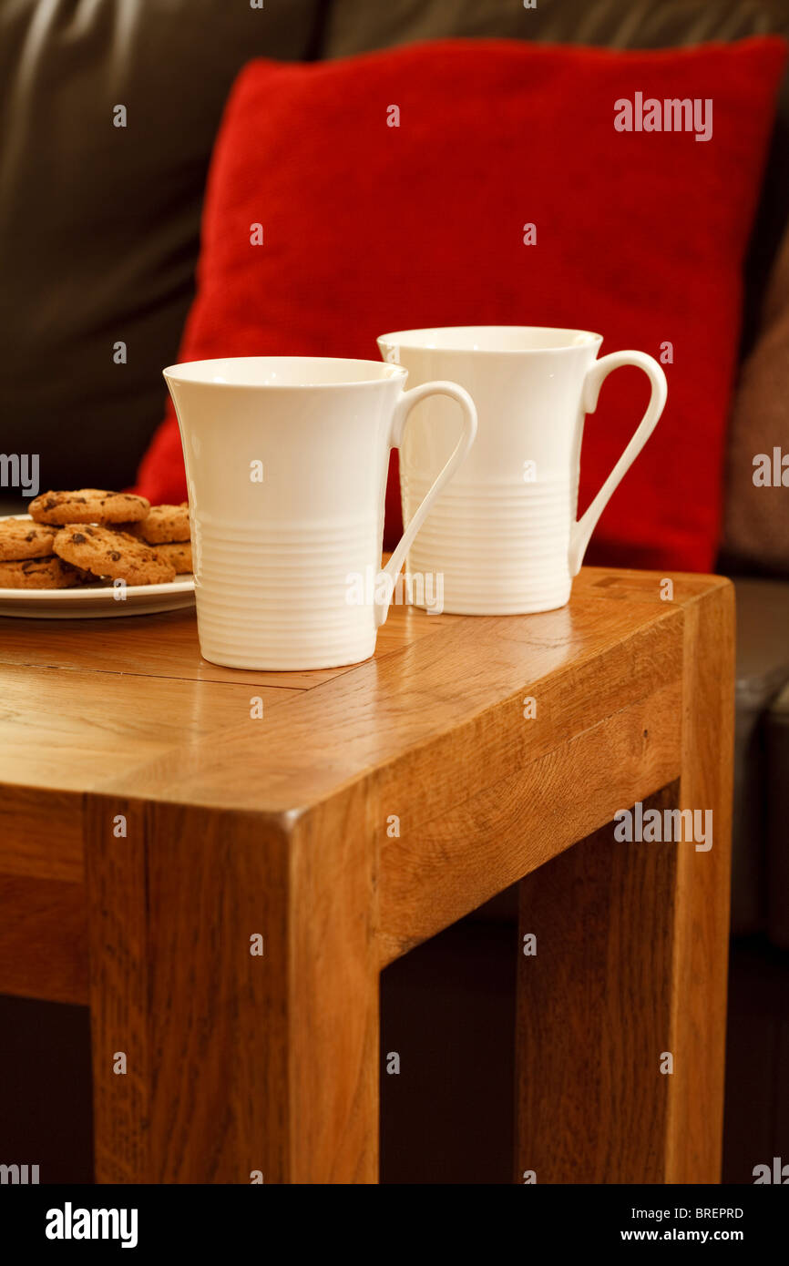 Detail of a modern interior with coffee mugs, cookies, coffee table, sofa and cushions - Stock Image