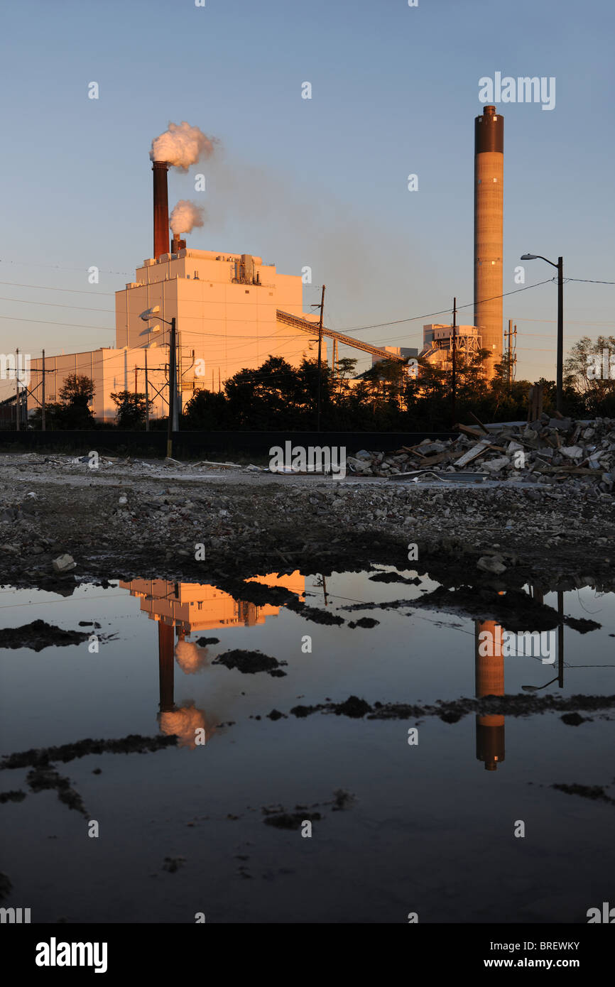 Industrial site with smokestacks with rubble and water reflections in foreground - Stock Image