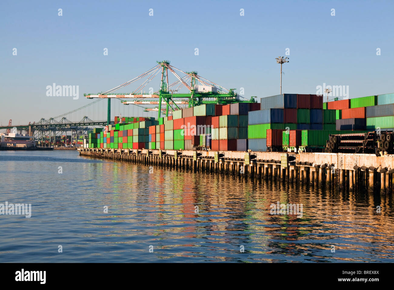 Shipping containers and harbor cranes in warm late afternoon light. - Stock Image