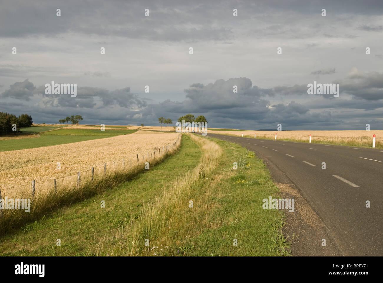 Road across farmland, Massif Central, France. Near Vallee du Lot. - Stock Image