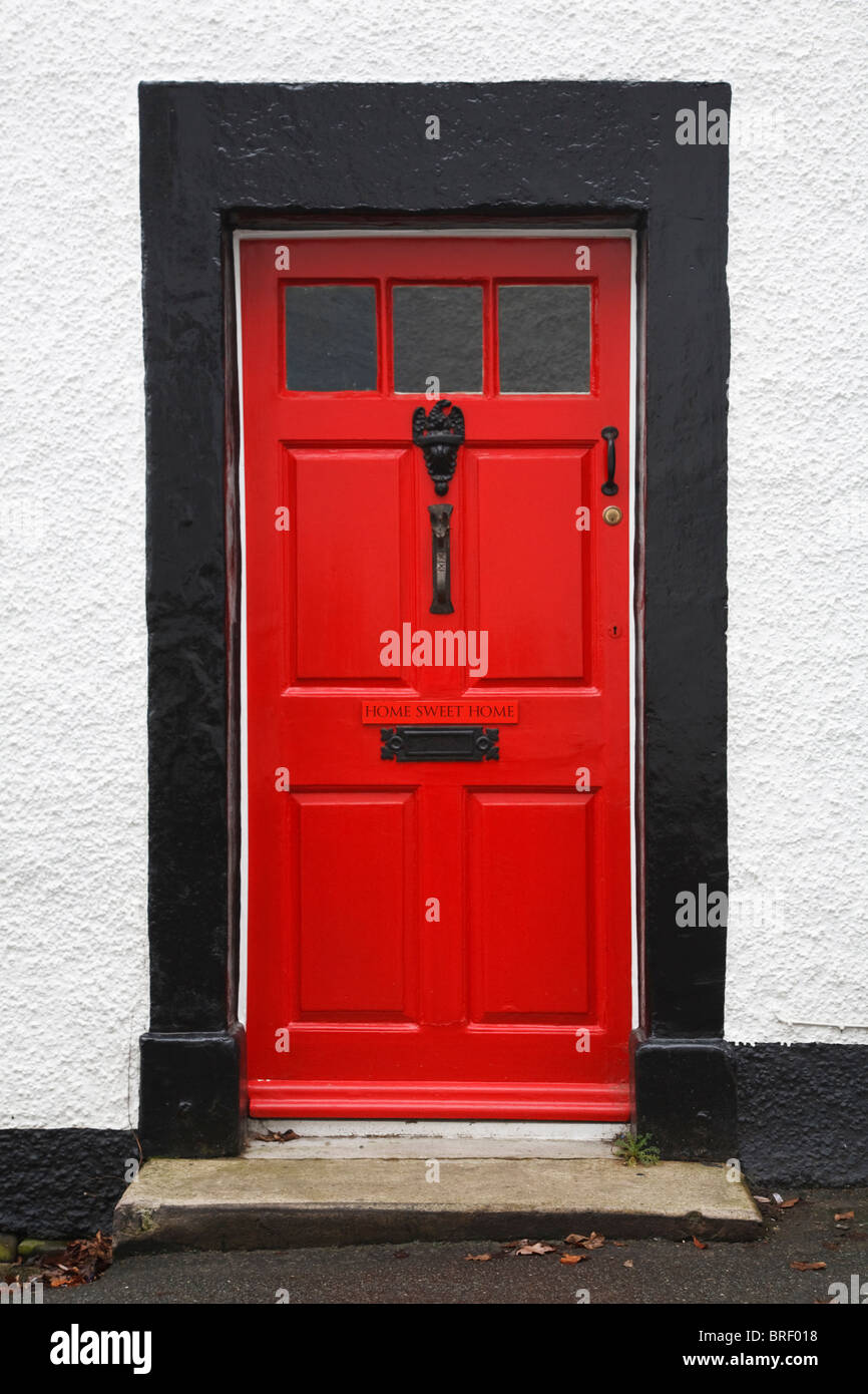 Front door of a traditional british house painted bright red and with a Home Sweet Home sign - Stock Image