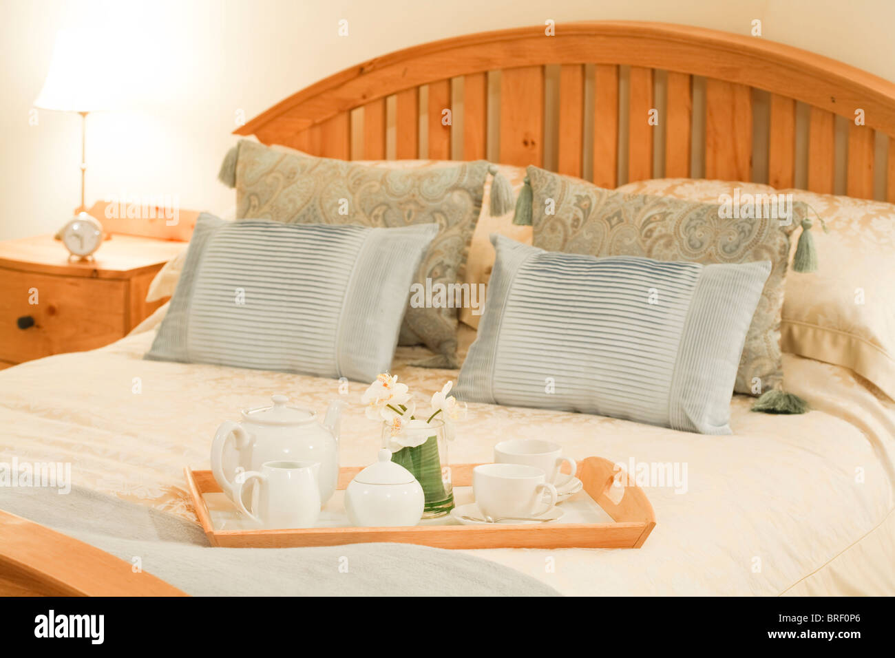 Room service tray on a bed in a luxury hotel bedroom with cozy bedlinen - Stock Image