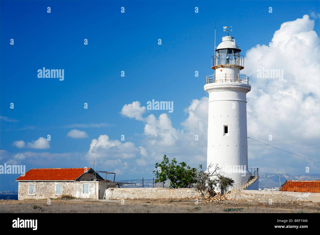 White lighthouse, house, red roof, blue sky, white clouds, Paphos, Pafos, Cyprus, Europe - Stock Image