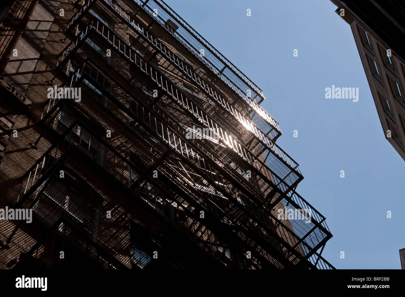Iron Fire Escape glinting in the sun. A multistory steel fire escape zigzags down the side of an old Boston high Stock Photo