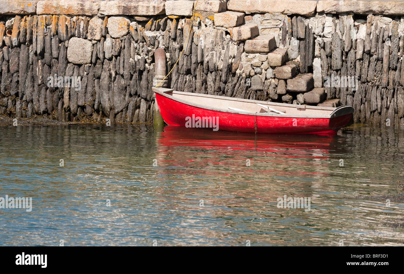 Steps to a red dingy. Rough stone steps lead down to a bright red dingy tied up to the harbor wall. - Stock Image