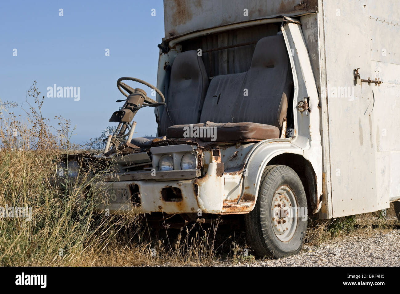 An old broken down Van left  to rust on a dusty road in Cyprus - Stock Image