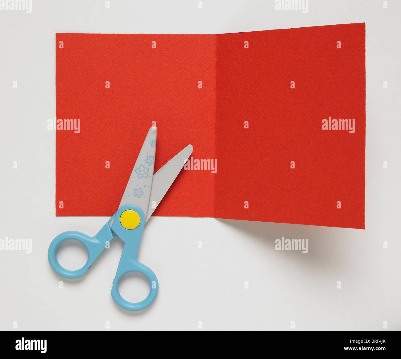 Sheet of red card with crease folded along centre, blue handled scissors - Stock Image