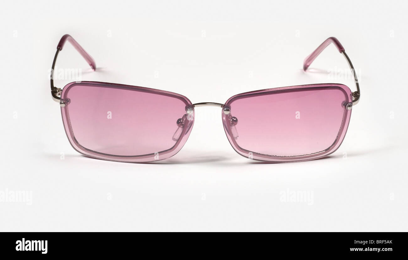 Pair of rose tinted square framed sunglasses on white surface - Stock Image