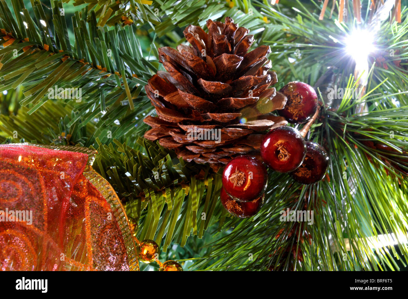 Christmas tree decorations light lights red gold parcel berry forest pine cone close up shot candy stick - Stock Image