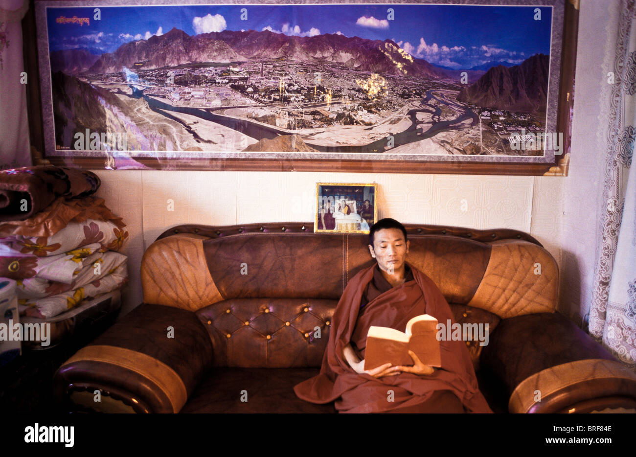 Tibetan buddhist monk Dongyu, reading the Buddha's teachings in his small but well equiped and furnished living - Stock Image