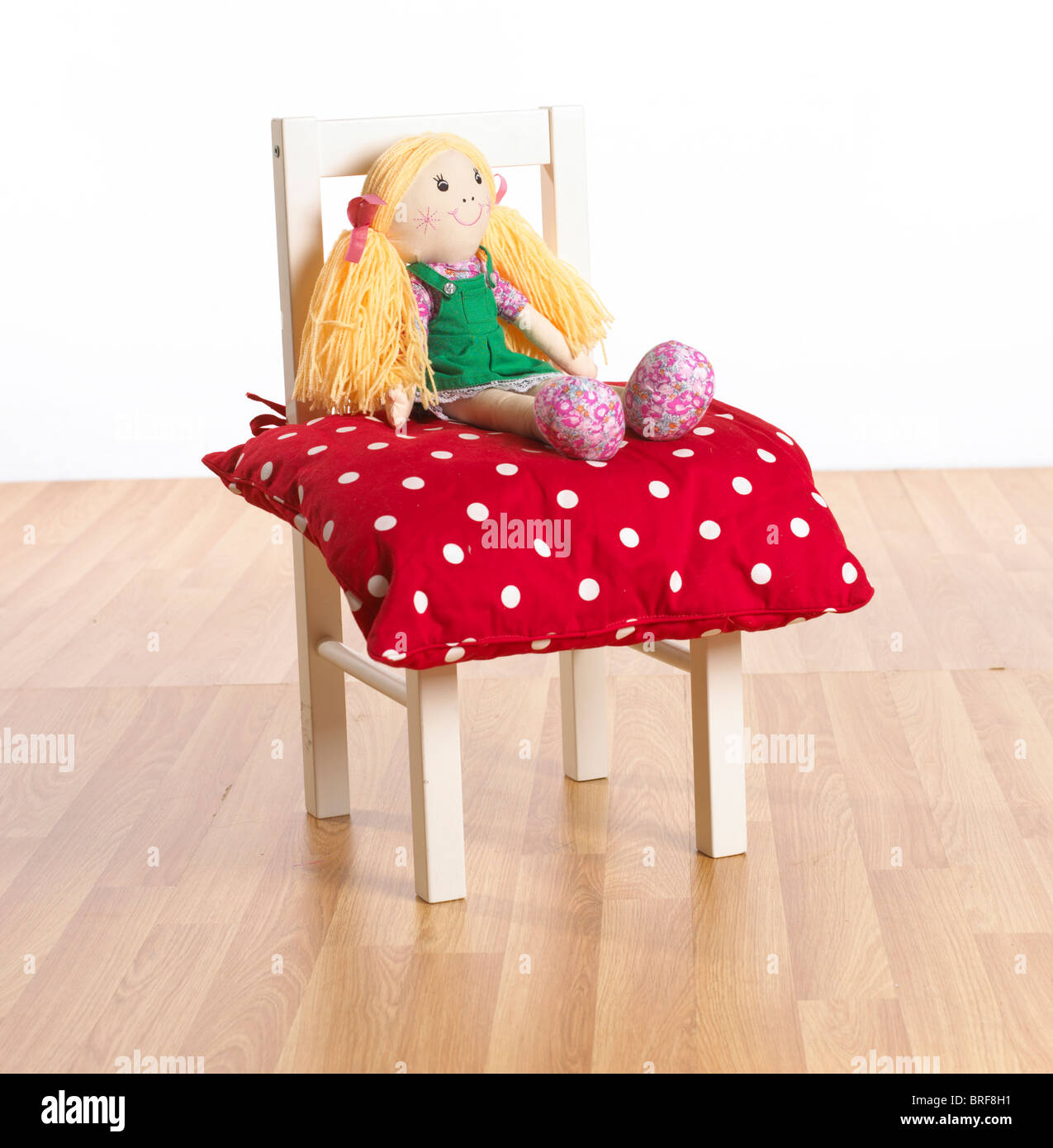 Rag doll sitting on red polka dot cushion on childs chair - Stock Image
