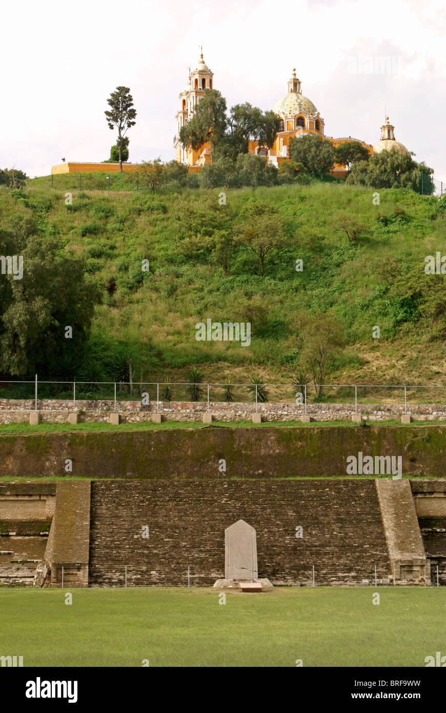 Pre-Hispanic ruins at southern base of Tepanapa Pyramid and Santuario de Nuestra Senora de los Remedios church, - Stock Image