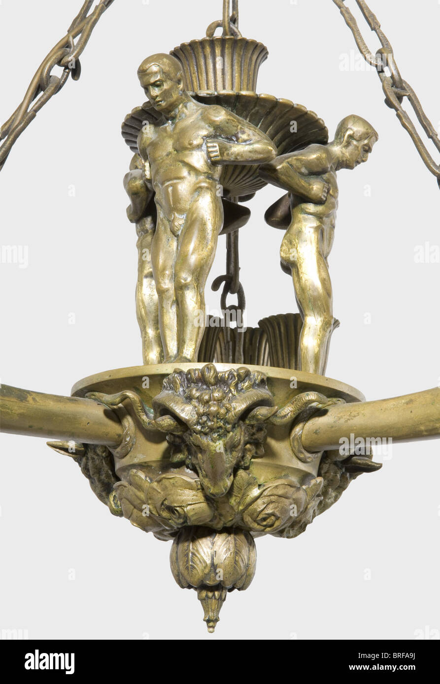A bronze ceiling light., Three arms in cornucopia form with male heads in relief circumferentially around the rim Stock Photo