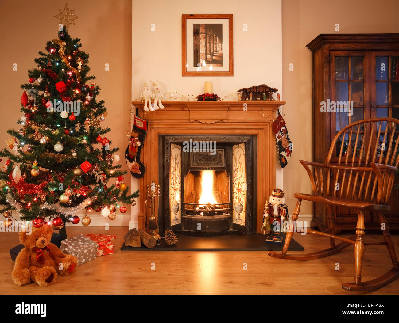 Living room with open fire, christmas decorations and tree. [Picture above fireplace is photographers own work] - Stock Image