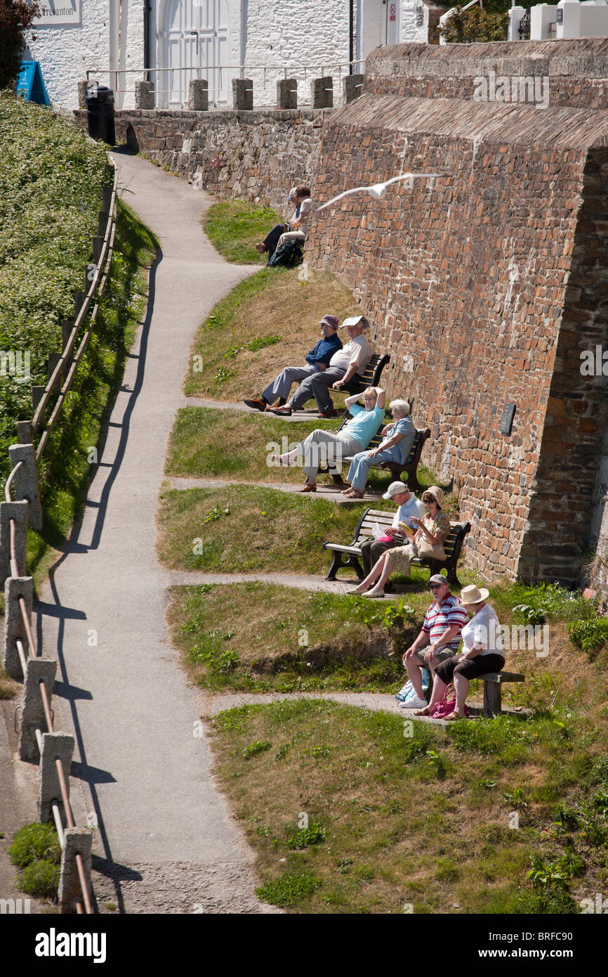 Ten People in pairs enjoying the harbour view. Five pairs of people occupy the benches in a narrow park below the - Stock Image