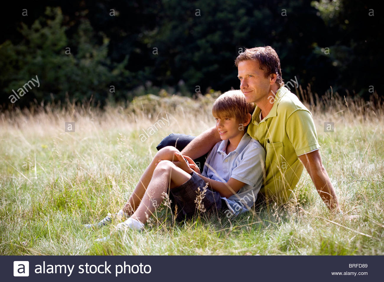 A father and son sitting on the grass - Stock Image