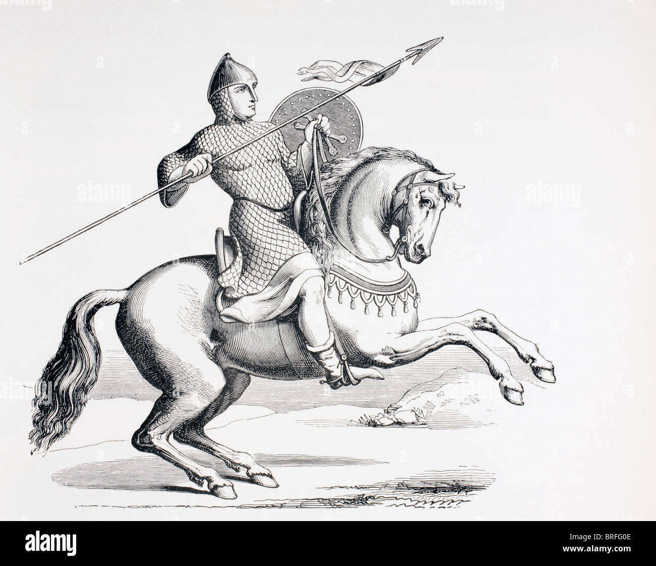 A Norman knight dressed in chain mail and helmet carrying spear and shield. - Stock Image