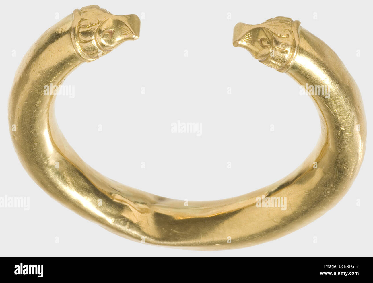 A golden Hellenistic bracelet, 3rd/2nd century B.C. Hollow, double tapered bracelet with stylized animal head finials. - Stock Image