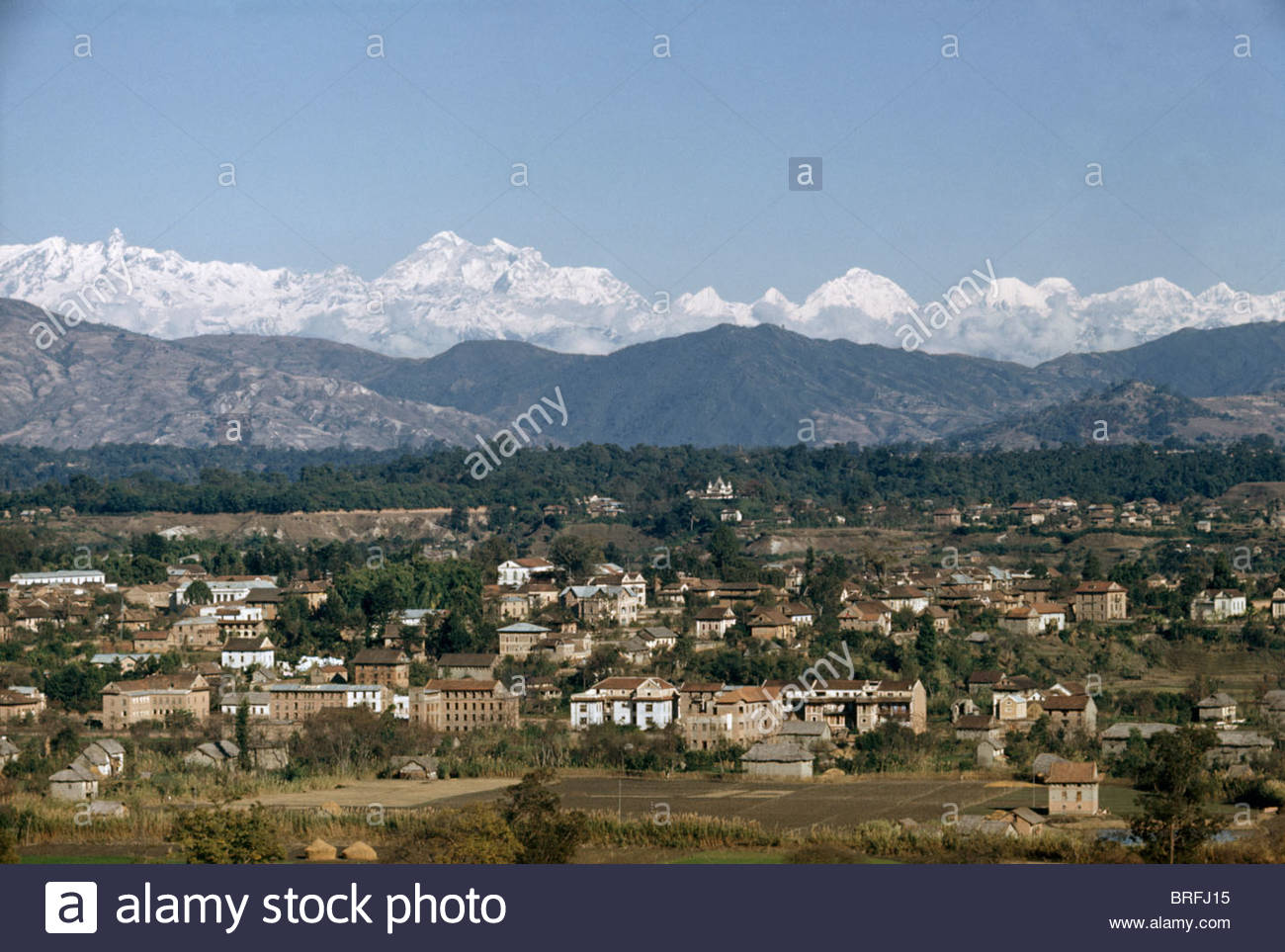 Katmandu sits in a valley; distant snowy mountains line horizon. - Stock Image